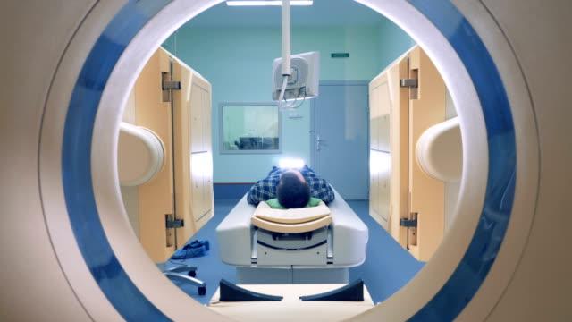 vídeos de stock, filmes e b-roll de verificação de equipamento médico e um paciente do sexo masculino. homem estabelece no dispositivo de imagem de ressonância magnética. - pré estreia