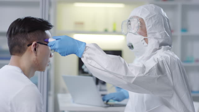 Medical Scientist in Hazmat Suit Checking Patients Temperature - vídeo
