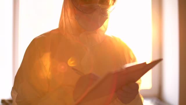 vidéos et rushes de spécialiste médical dans l'écriture de combinaison protectrice sur le presse-papiers, recherche du virus - bloc note