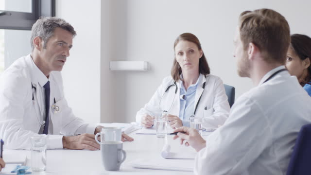 medical staff discussing at conference table - collega d'ufficio video stock e b–roll