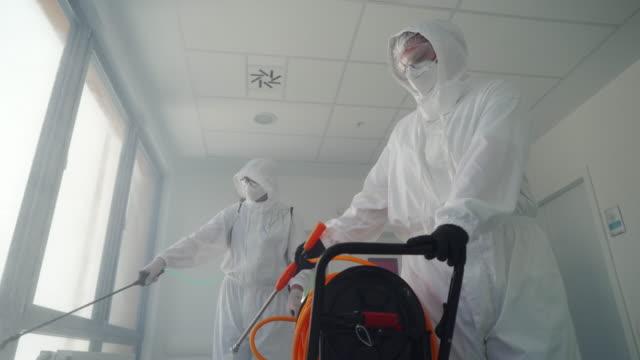 il personale medico sta disinfettando l'ospedale locale - addetto alle pulizie video stock e b–roll
