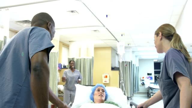 vídeos de stock e filmes b-roll de medical staff moving patient on gurney in hospital ward - empurrar atividade física