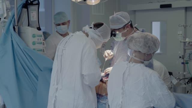 vídeos de stock, filmes e b-roll de equipe médica da unidade operacional faz cirurgia cardíaca - marcapasso cirurgia cardíaca