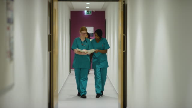 Medical Staff Walking Through Hospital Front view of a Caucasian and an African American female medical worker in a hospital corridor, wearing scrubs, reading a patient file and talking, walking towards camera, with other hospital staff walking in the background and foreground, slow motion nhs stock videos & royalty-free footage