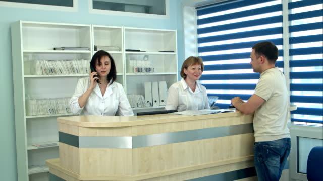 medicinsk personal som arbetar på upptagen medicinsk reception - hospital studio bildbanksvideor och videomaterial från bakom kulisserna