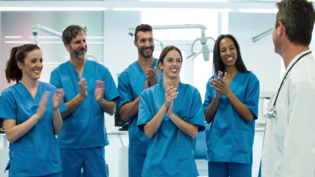 Medical team applauding doctor after a successful day video