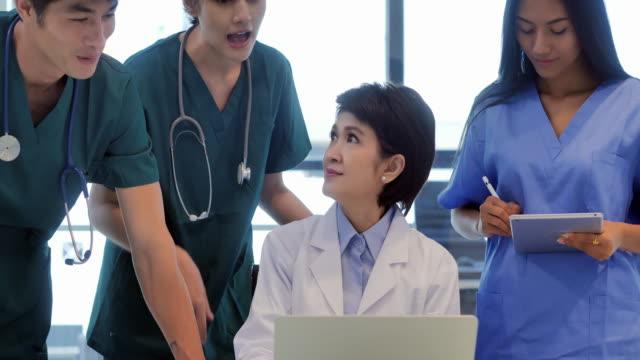 läkarteam som har ett möte med läkare kvinnor på datorn. team av experter läkare undersöker läkarundersökningar. medicinsk utbildning, hälsovård, medicinsk pedagogik, teknik, människor och medicin koncept. utbildningsämnen. kvinnor i stem - ledarskap bildbanksvideor och videomaterial från bakom kulisserna