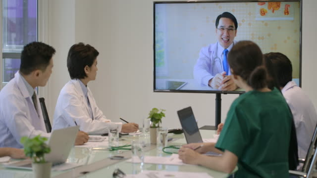 病院の会議室でオンラインビデオ会議を持つ医療チーム。 - テレビ会議 日本人点の映像素材/bロール