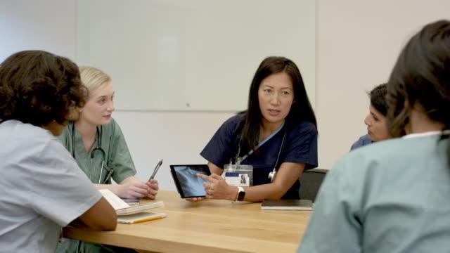 toplantıda sağlık ekibi - cerrahi önlük stok videoları ve detay görüntü çekimi