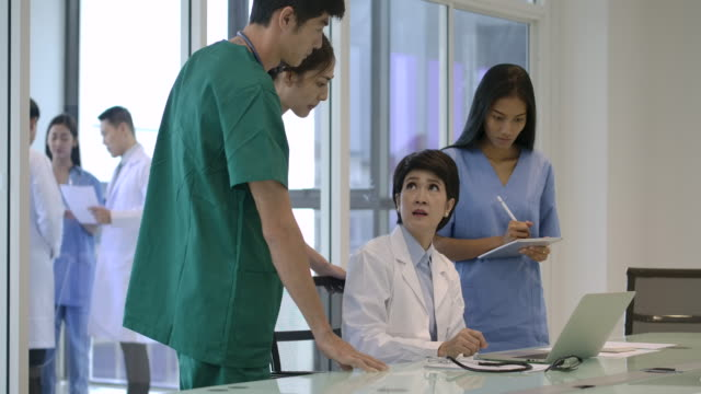 zespół medyczny 4k w nowoczesnym szpitalu patrząc na komputer & spotkanie w sali konferencyjnej. - klinika filmów i materiałów b-roll