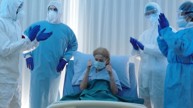 vídeos de stock e filmes b-roll de medical team in virus protective suit feeling happy and clapping hands together to coronavirus covid-19 infected senior patient - melhoria