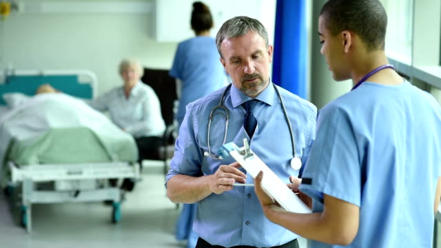 medical team meeting on the hospital ward a mture gp chats to a  young male nurse discuss  a patient's case on thehospital ward . They are all wearing blue medical scrubs. In the background a hospital bed with a patient in it is visited by a senior relative . A female nurse wheels a trolley into their cubicle. nhs stock videos & royalty-free footage