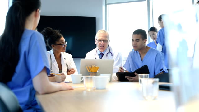 medical team meeting A medical team sit around a conference table and discuss something . general practitioner stock videos & royalty-free footage