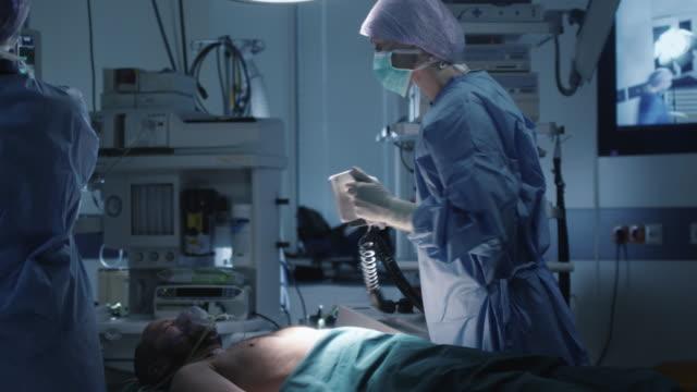 vídeos de stock e filmes b-roll de medical team performing defibrillation in modern operating room - ataque cardíaco
