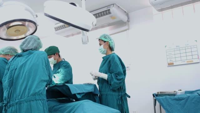 vídeos y material grabado en eventos de stock de médico equipo realizar operación quirúrgica en room.multi funcionamiento moderno equipo quirúrgico étnicos en ropa protectora realizar cirugía hospital quirófano - columna vertebral humana