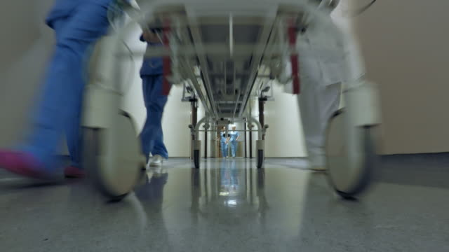 POV Medical team pushing a stretcher down the hospital hallway Point of view low angle shot of a medical team pushing a stretcher with patient down the hallway in a hospital. stretcher stock videos & royalty-free footage