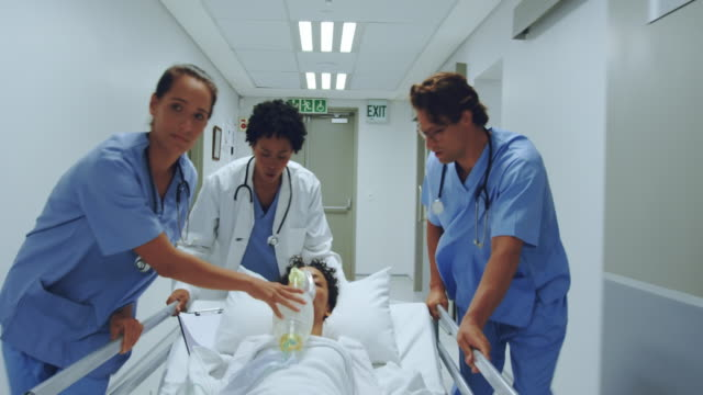 medical team pushing emergency stretcher bed in the corridor at hospital Front view of diverse medical team pushing emergency stretcher bed in the corridor at hospital. Female doctor holding oxygen mask stretcher stock videos & royalty-free footage