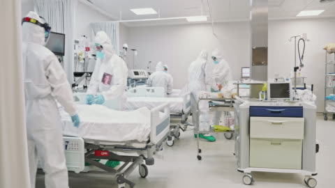 Medical Team Rolling Senior Male Patient into ICU Healthcare workers in full protective suits wheeling gurney with senior male COVID-19 patient on ventilator into ICU. covid stock videos & royalty-free footage