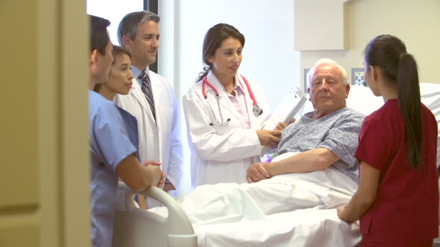 vídeos y material grabado en eventos de stock de equipo médico hablando al paciente senior en hospital - geriatría