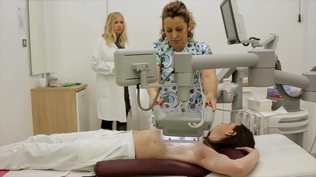 stockvideo's en b-roll-footage met medisch technicus voorbereidt patiënt in borstonderzoek op de meest moderne echografie-apparaat - breast cancer