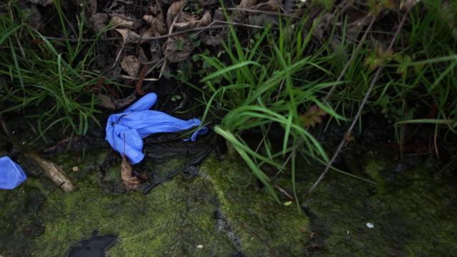 vídeos y material grabado en eventos de stock de la basura médica está en el suelo en un parque. reciclaje de máscaras y guantes médicos. coronovirus covid-19 y la ecología del planeta - guante quirúrgico