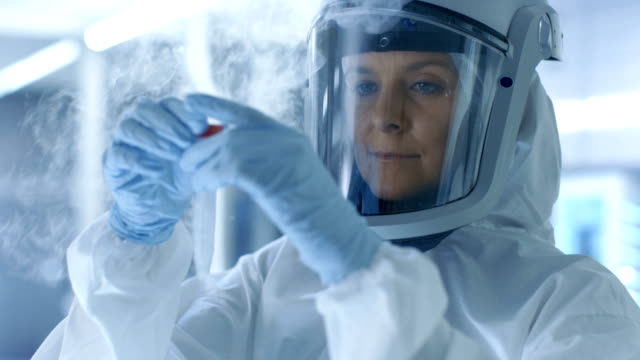 Medical Virology Research Scientist in a Hazmat Suit with Mask, She Inspects Test Tube with Isolated Virus String from Refrigerator Box. She Works in a Sterile High Tech Laboratory/ Research Facility. video