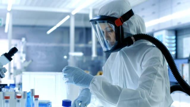 Medical Virology Research Scientist Works in a Hazmat Suit with Mask, She Uses Micropipette. She Works in a Sterile High Tech Laboratory, Research Facility. video