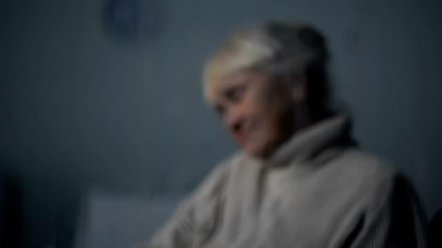 雨の夜に毛布と医療従事者の覆い古い眠っている女性のケアします。 - 介護点の映像素材/bロール