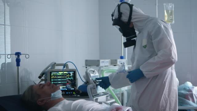 medicinsk arbetstagare sätter en andningsapparat på en patient - intensivvårdsavdelning bildbanksvideor och videomaterial från bakom kulisserna