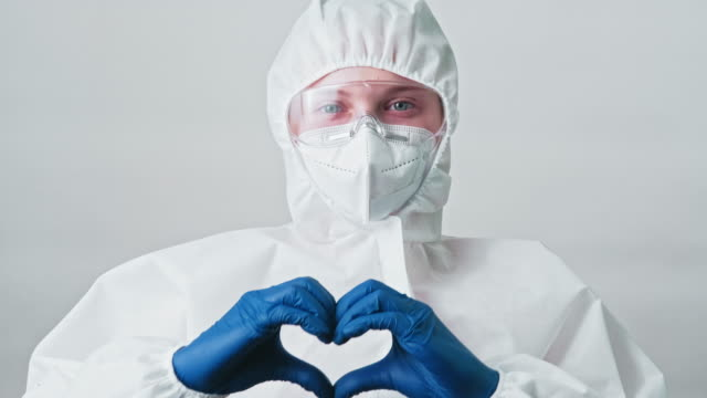 medical worker nurse googles face mask heart sign - google filmów i materiałów b-roll
