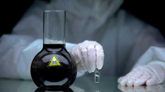 vídeos y material grabado en eventos de stock de trabajador médico poniendo ampolla con antídoto en la mesa cerca de veneno en matraz - señalización vial