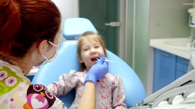 vídeos y material grabado en eventos de stock de medicina y cuidado de la salud, médico de la mujer en guantes de goma con herramienta especial trata los dientes de niña alegre - ortodoncista