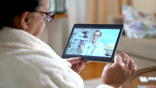 Medicine online. Elderly woman consulting with her physician using video chat at home