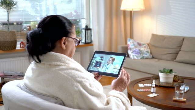 vídeos de stock e filmes b-roll de medicine online. elderly woman consulting with her physician using video chat at home - etnia