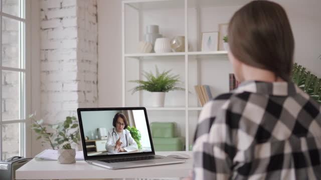 läkemedel på nätet. ung kvinna är samråd med kvinnlig läkare använder videochatt hemma - videor med medicinsk undersökning bildbanksvideor och videomaterial från bakom kulisserna