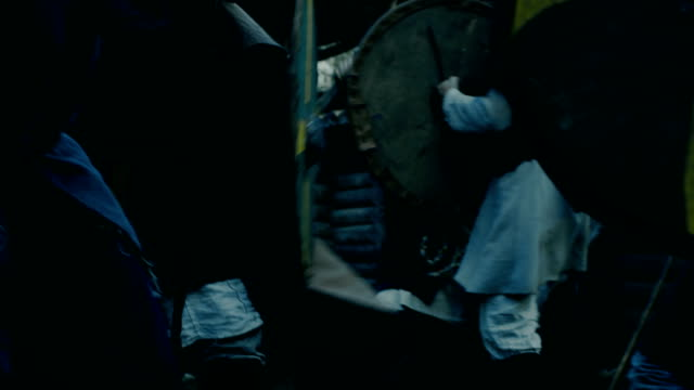 ortaçağ savaş reenactment. savaşçı saldırı korumaları ve tahta kale sivil şiddet kabilesi. balta, kılıç ve kalkanlar ile kavga ediyorlar. - ortaçağ stok videoları ve detay görüntü çekimi