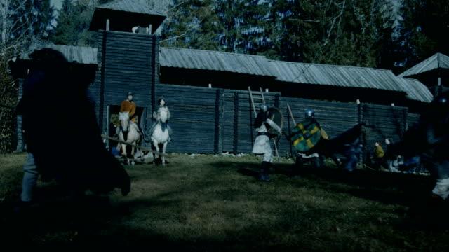 vídeos y material grabado en eventos de stock de batalla medieval donde defender a vikings ataque wooder fortaleza, aldeanos y lucha. las mujeres con caballos corren por sus vidas. recreación medieval. - vikingo