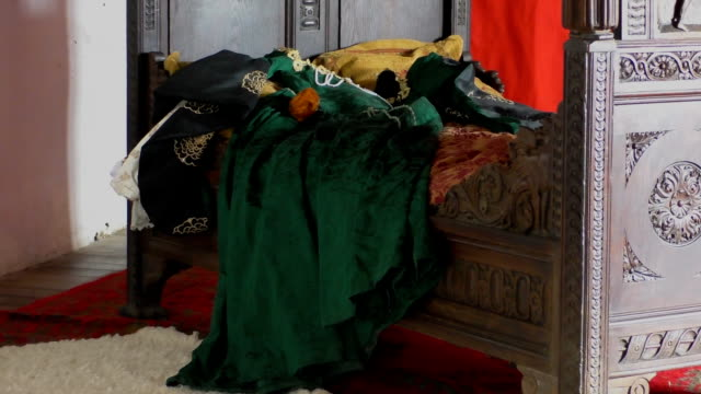 Medieval bed Old green dress on medieval ornamental wooden bed and rug on the floor 19th century style stock videos & royalty-free footage