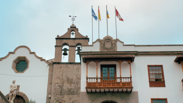 Tenerife, Canary Islands, Spain - January, 2019: Medieval building with flags and bell tower in spain. Carved wooden balcony