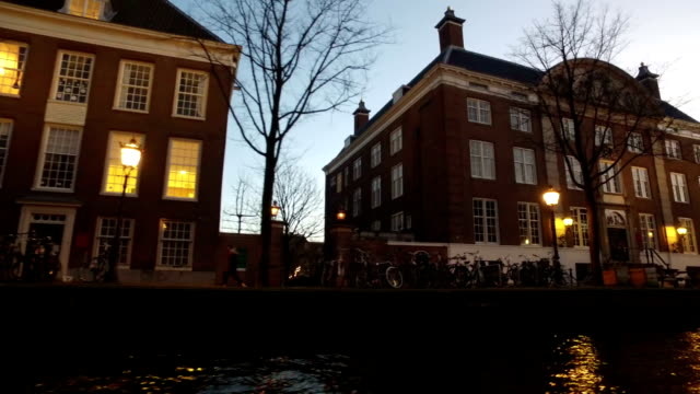 Medieval buildings along the canals in Amsterdam Netherlands at sunset video