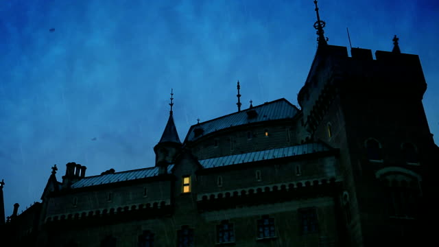 Medieval castle scene: lights appearing gradually in the windows as the dusk descends. A flock of birds passing above the roof. video