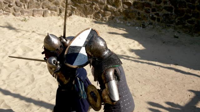 stockvideo's en b-roll-footage met middeleeuwse duel vechten in harnas op zwaarden - ridderlijkheid