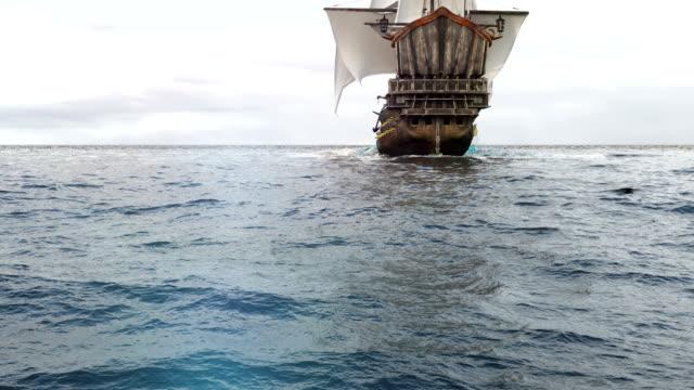 en medeltida fregatt som seglar på ett gränslöst blått hav. begreppet havsäventyr under medeltiden. - segelfartyg bildbanksvideor och videomaterial från bakom kulisserna