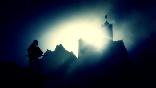 medieval knight looking at a dark castle - mitologia video stock e b–roll