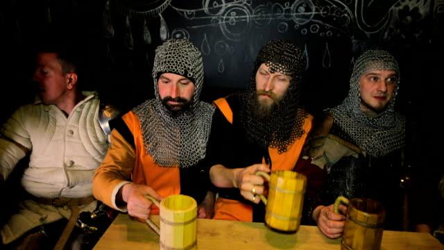 Medieval knights drink beer on dark background