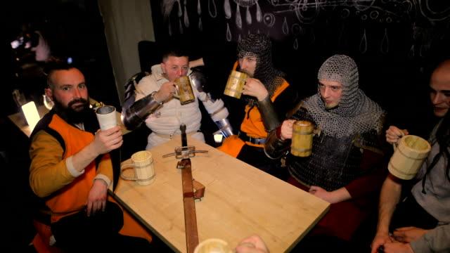stockvideo's en b-roll-footage met middeleeuwse ridders drinken bier op donkere achtergrond - middeleeuws