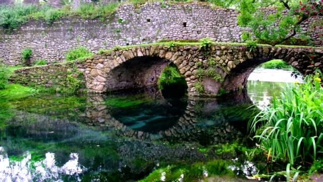 ponte medievale in pietra in giardino colorato eden vibrante con rose e fiume - giardino pubblico giardino video stock e b–roll