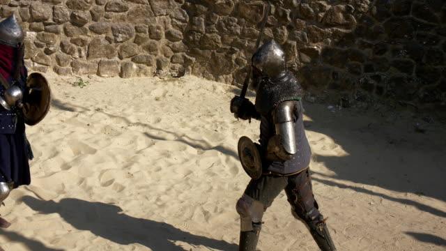 stockvideo's en b-roll-footage met middeleeuwse toernooi. twee sterke krijger ridders vechten in arena - ridderlijkheid