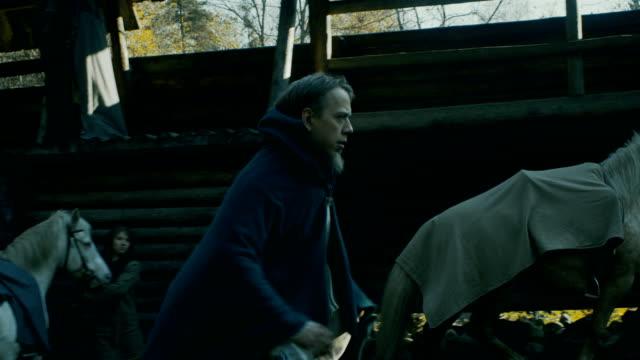 中世の村の生活の再現。木造の要塞、長老のメッセージが付いている壁に沿って実行している若い男のヤードでの生活。馬と村人たち。 - 田舎のライフスタイル点の映像素材/bロール