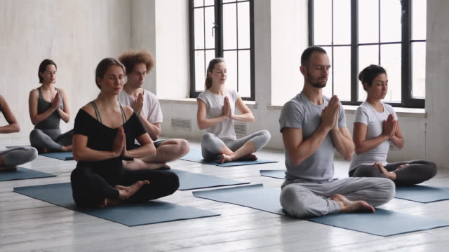 Meditating diverse people seated in lotus pose practicing yoga indoors Male coach and group of diverse people seated in lotus pose folded hands Namaste symbol practicing yoga meditating during class, prayer position, spiritual practice, lifestyle life philosophy concept lotus position stock videos & royalty-free footage
